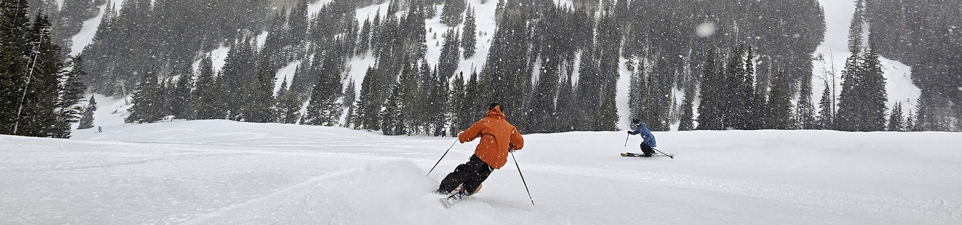 Two skiers at Breckenridge on powder day 1920x450